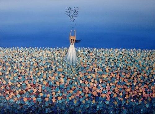 Kobieta na łące z sercem z ptaków