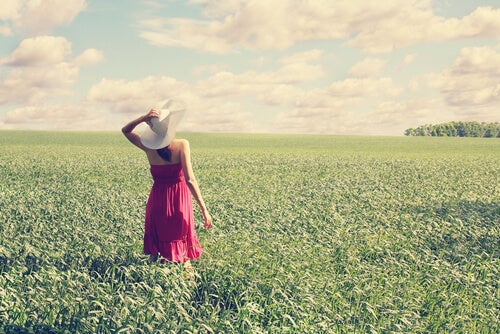Kobieta na polanie w czerwonej sukience i z kapeluszem na głowie