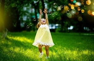 Dziecko bawiące siębańkami mydlanymi
