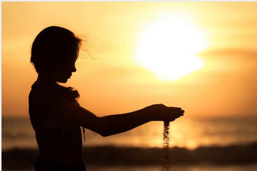Dziewczynka na plaży przesiewająca piasek