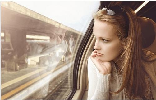Kobieta patrząca przez szybęw pociągu