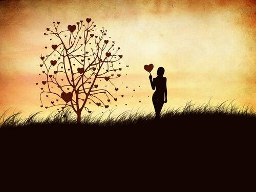 Kobieta z sercem obok drzewa