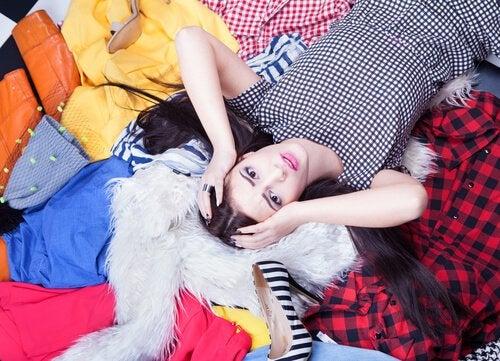 Kobieta z wieloma ubraniami trzymająca się za głowę
