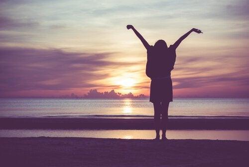 osoba na plaży wyciąga ręce