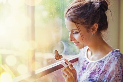 Kobieta przy oknie obserwuje motyla