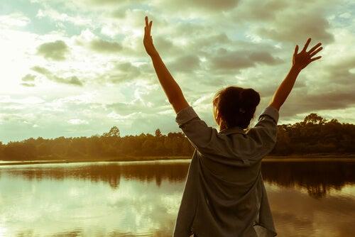 Szczęśliwa kobieta wznosi ręce