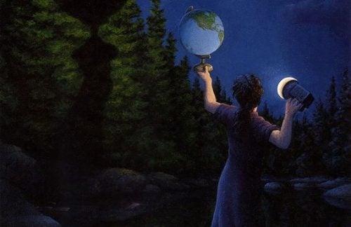 człowiek z globusem w lesie