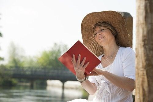 Kobieta w kapeluszu czyta książkę