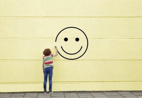 Kobieta rysuje uśmiech na ścianie