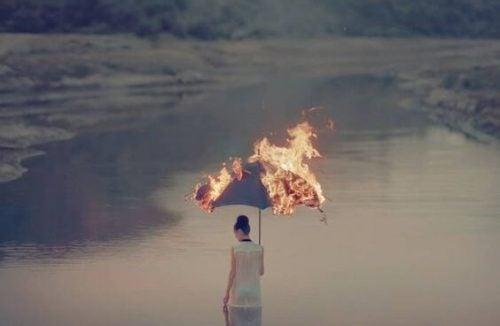 kobieta stoi w wodzie z płonącym parasolem