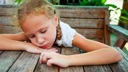 Smutna dziewczynka przy stole
