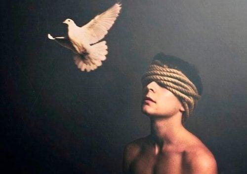 mężczyzna z zawiązanymi oczami i gołąb