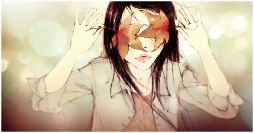Dziewczyna zasłaniająca sobie oczy liśćmi klonu