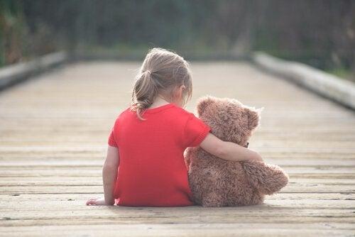 Dziewczynka z misiem siedzi na moście