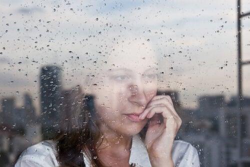 Kobieta wyglądająca przez okno podczas deszczu
