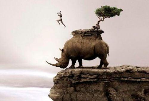 Człowiek skacze z nosorożca
