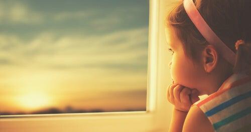Mała dziewczynka patrząca przez okno