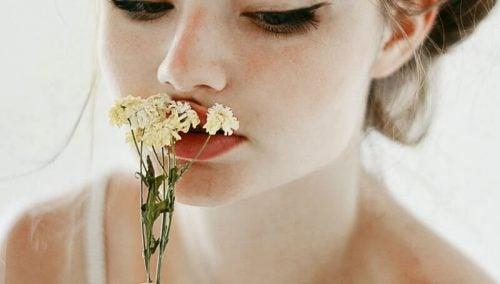 Kobieta w bieli trzymająca kwiat