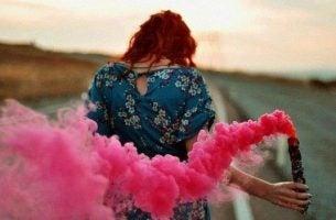 Kobieta za którą ciągnie się różowy dym
