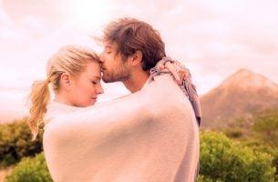 Mężczyzna całuje kobietę w czoło