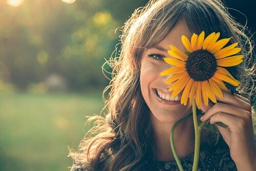 Uśmiechająca się kobieta z kwiatkiem