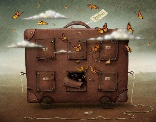 Latające motyle wokół walizki