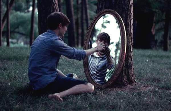 Chłopak w lesie dotyka lustra.