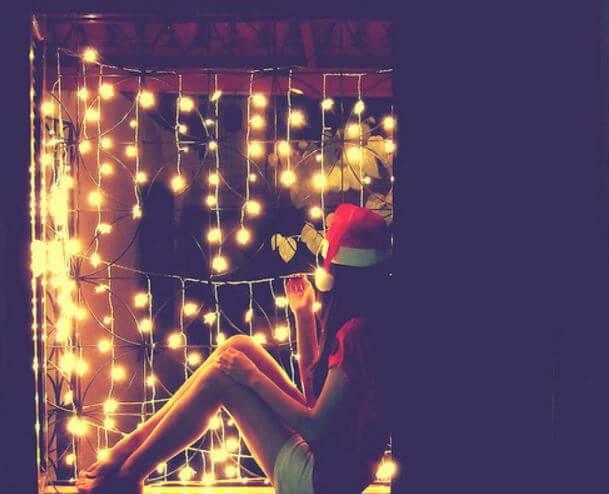 Dziewczyna w czapce Mikołaja siedzi przy lampkach świątecznych.