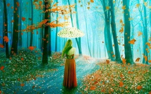 Komplementy są jak liście na wietrze dla kobiety w lesie z parasolką