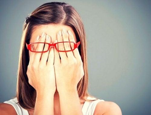 Kobieta skrywa twarz w dłoniach