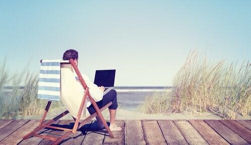 mężczyzna siedzi z laptopem na plaży