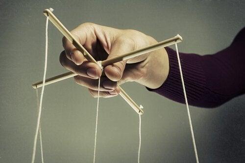 Mężczyzna trzyma sznurki od marionetki.