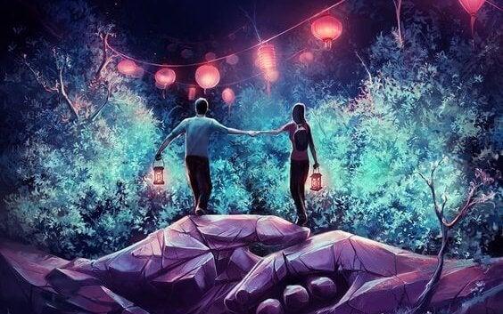 Para z latarenkami stojąca na splecionych dłoniach olbrzyma.