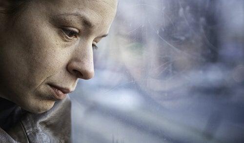 smutna kobieta patrzy w okno