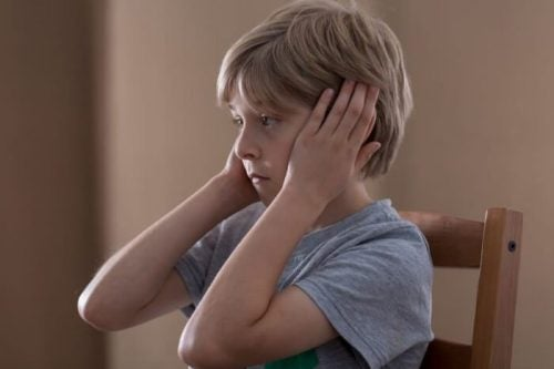 Chłopiec zakrywa swoje uszy