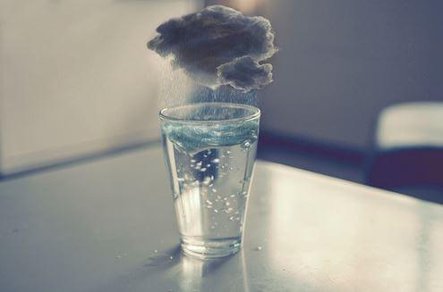 Deszczowa chmura wisi nad szklanką wody.