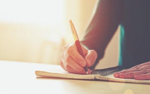 Człowiek pisze w zeszycie