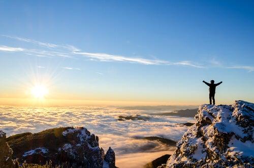 Nie chciał się poddać - Człowiek na szczycie góry patrzy na słońce