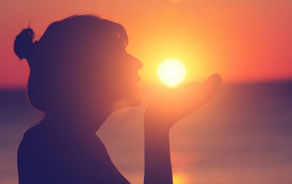 Dziewczyna podtrzymuje dłońmi słońce podczas zachodu