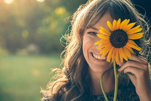 Dziewczyna uśmiecha się i trzyma słonecznik