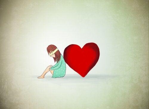 Dziewczyna z zawiązanymi oczyma obok wielkiego serca