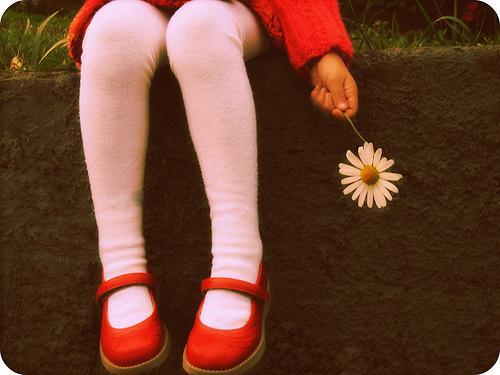 Dziewczynka z kwiatkiem w dłoni.