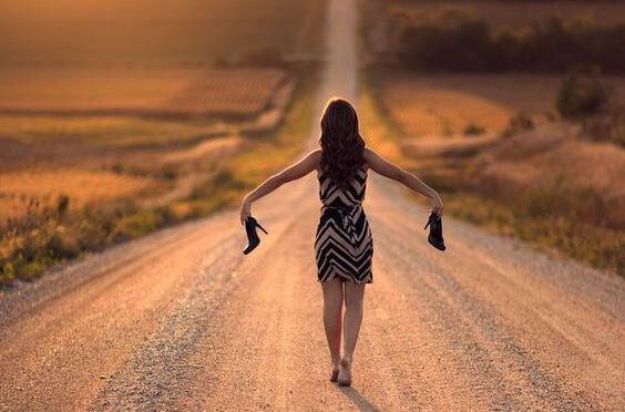Kobieta idzie drogą bez butów.