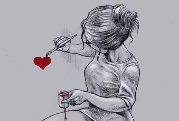 Dziewczyna maluje serce na ścianie.