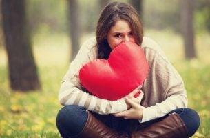 Dziewczyna trzyma w dłoniach poduszkę - serce.