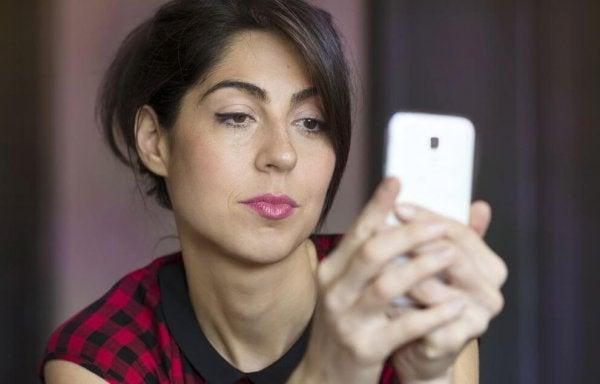 Zazdrość - kobieta sprawdzająca telefon.