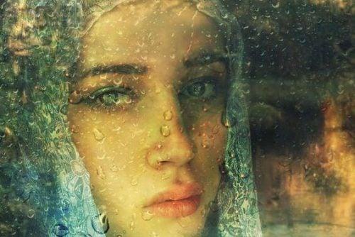 smutna dziewczyna patrzy przez okno