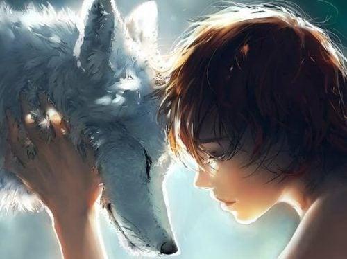 Wilk i chłopiec przytulają się czołem do czoła