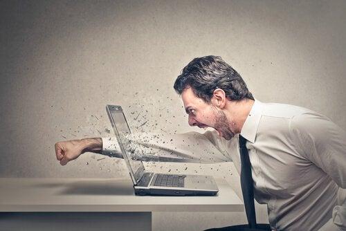 Wciekły mężczyzna przebiją ręką ekran laptopa.