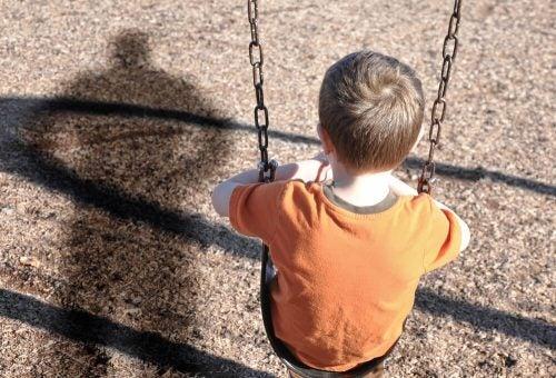 Pezmoc - chłopiec na huśtawce i cień rodzica